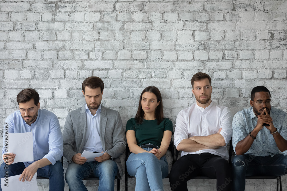 Fototapeta Expecting employer decision. Worried nervous multiethnic young people candidates on vacant place sitting in row at office hall waiting for private conversation with hr or announcing competition result