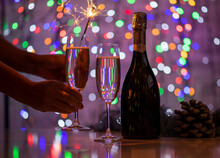 Girl Holding A Bengali Fire And A Glass Of Champagne On A Beautiful Festive Bokeh Background, Consisting Of Colored Out Of Focus Lights On A Dark Background