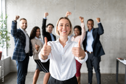 Businesswoman Gesturing Thumbs-Up Standing With Joyful Employees Team In Office