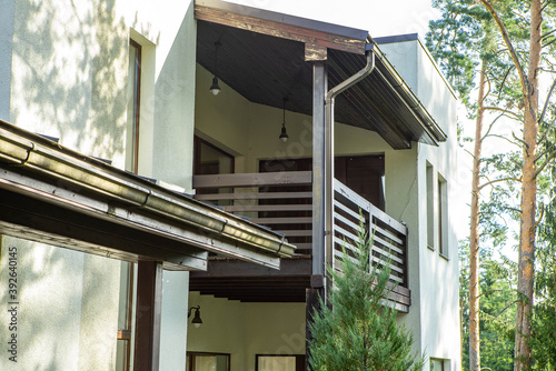 Modern exterior of luxury cottage. Close-up of wooden terrace under wooden roof on second floor. Huge pines. White wall.