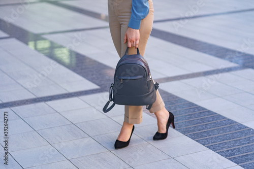 Fototapeta Woman wearing classic black high heel toe shoes while posing with a gray leather backpack
