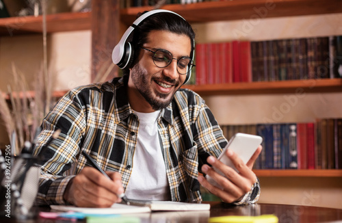 Fotografia Happy Indian Student With Smartphone Learning Sitting In University Library