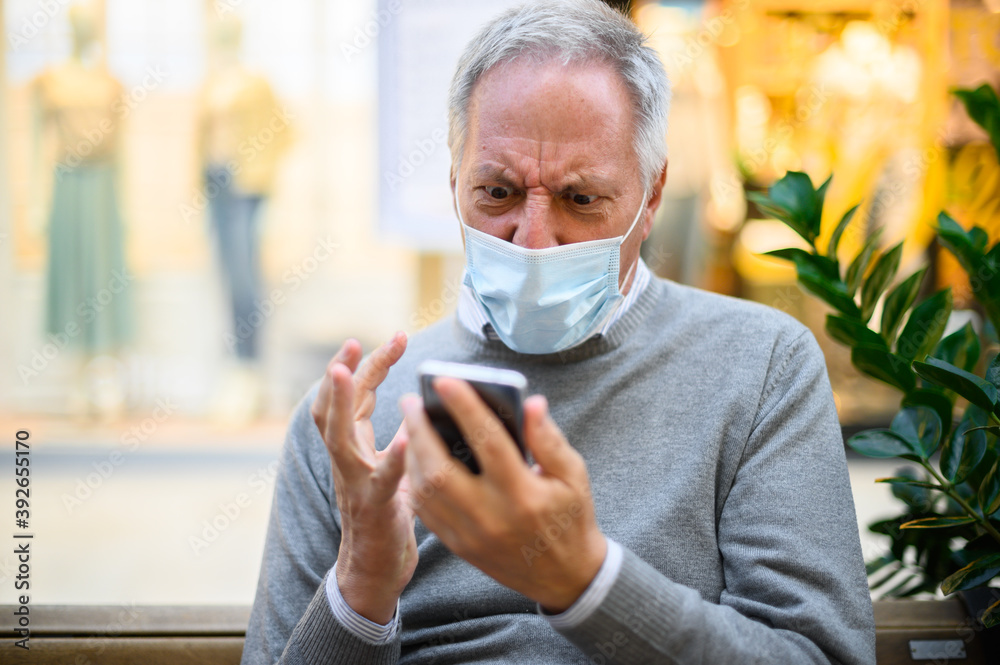 Fototapeta Senior man sitting on a bench and using a smartphone in a mall wearing mask and getting angry, coronavirus concept