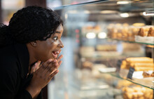 Surprised Amazed Happy African American Millennial Lady With Open Mouth Looks At Shop Window With Desserts