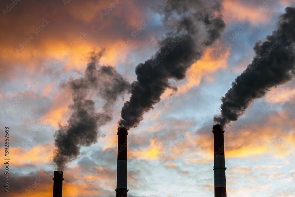 Fototapeta Three Smoking chimneys in dramatic colorful sky background. The concept of air pollution and the environment