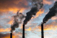 Three Smoking Chimneys In Dramatic Colorful Sky Background. The Concept Of Air Pollution And The Environment