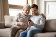 Leinwandbild Motiv Happy older father and adult son hugging, using phone at home together, smiling mature grandfather and grandson looking at screen, browsing apps, young man teaching senior dad to use smartphone