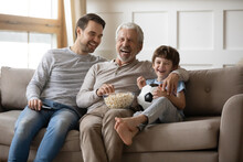 Laughing Little Boy With Grandfather And Father Watching Tv, Eating Popcorn Snack, Sitting On Couch With Soccer Ball, Happy Family Watching Football Game, Spending Leisure Time At Home Together