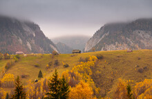 Villages In Romania, Amazing View Of The Authentic Places From Rucar-Bran Area At The Bottom Of Bucegi And Piatra Craiului Mountains During An Autumn Foggy Cloudy Day With Great Colors