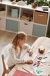 Leinwandbild Motiv Vertical high angle portrait of blonde teenage girl doing homework while sitting at desk in home interior, copy space