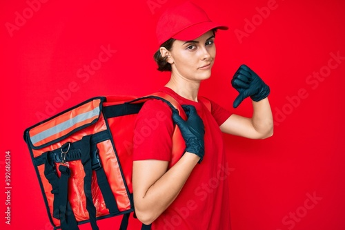Young hispanic woman holding take away backpack with angry face, negative sign s Fototapeta