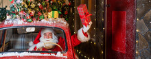 Santa Claus Delivers Presents Behind The Wheel Of A Red Car And Waves A Gift Box Out Of The Window