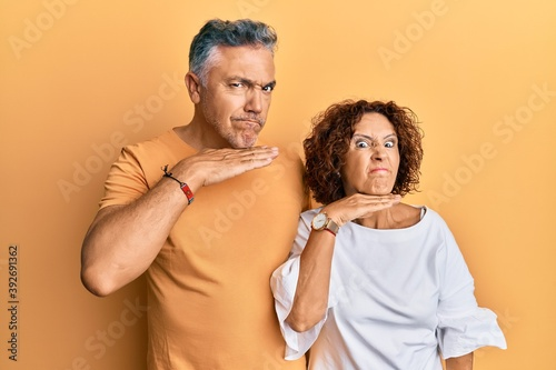 Fotografering Beautiful middle age couple together wearing casual clothes cutting throat with