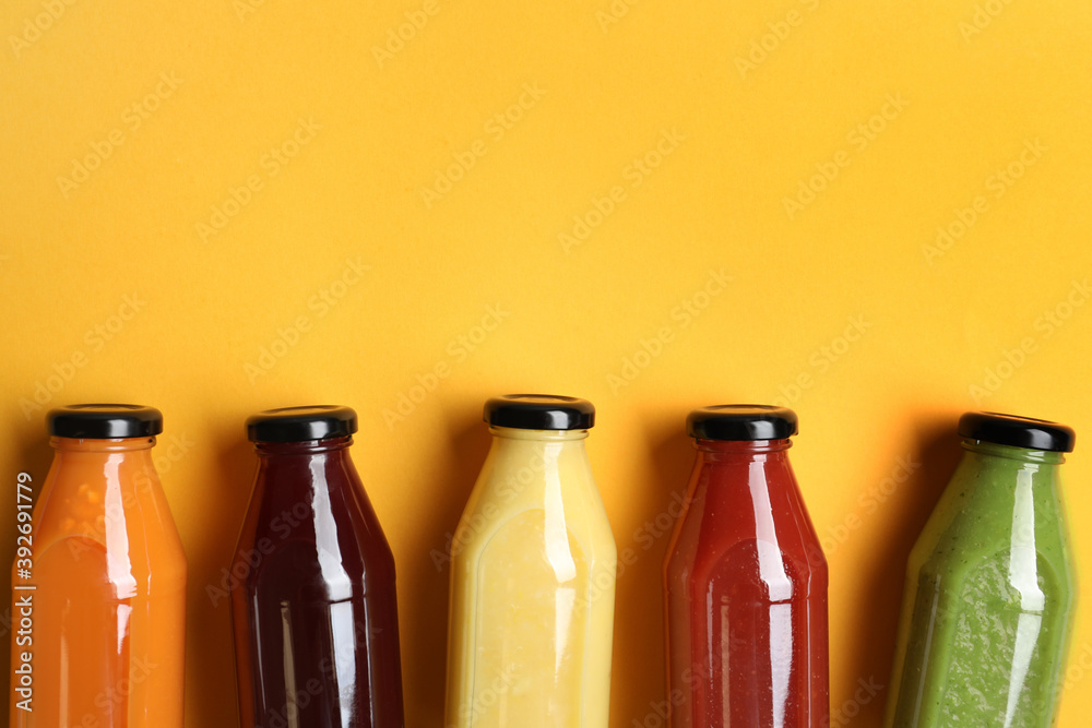 Fototapeta Bottles with delicious colorful juices on yellow background, flat lay. Space for text