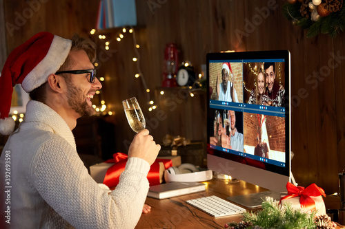 Happy young man wearing santa hat drinking champagne talking to friends on virtual video call meeting celebrate New Year party in holiday distance online conference chat together on computer at home.