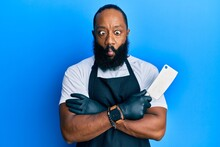 Young African American Man Wearing Professional Apron Holding Knife Making Fish Face With Mouth And Squinting Eyes, Crazy And Comical.