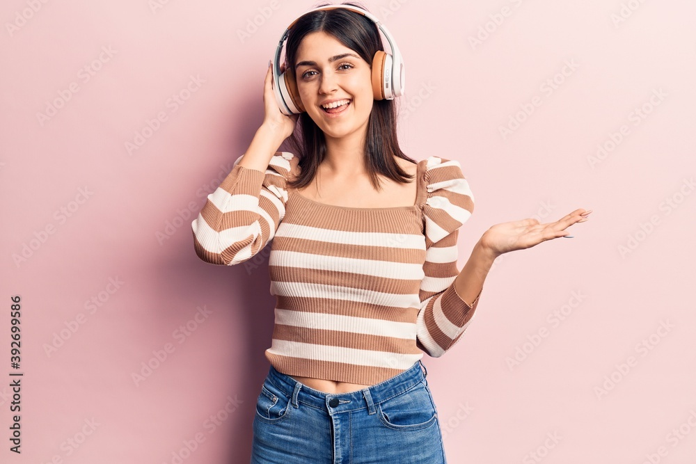 Fototapeta Young beautiful girl listening to music using headphones celebrating achievement with happy smile and winner expression with raised hand
