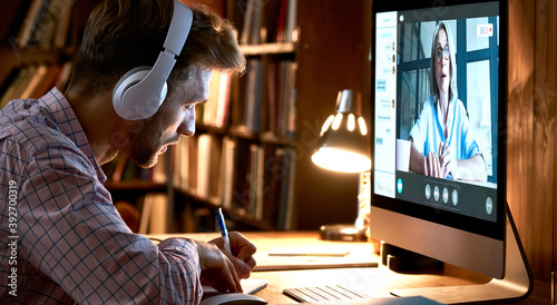Male student wearing headphones conference video calling, watching webinar, online training class, virtual chat meeting with remote teacher or coach distance learning using computer, taking notes.