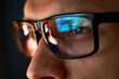 Close up view of focused businessman wears computer glasses for reducing eye strain blurred vision looking at pc screen with computer reflection using internet, reading, watching, working online late.