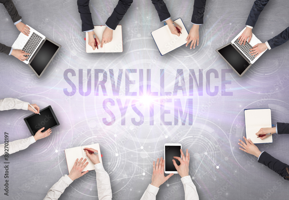Fototapeta Group of people in front of a laptop with SURVEILLANCE SYSTEM insciption, web security concept