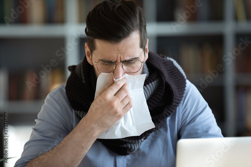 Fotografija Sick male office employee cover neck with warm scarf hold paper tissue blowing r