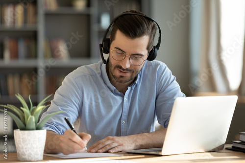 Focused 35s man sit at desk wear headphones watch webinar use laptop gain new knowledge writing notes. Video conference communication, negotiation remotely, study online, e-learn, self-educate concept