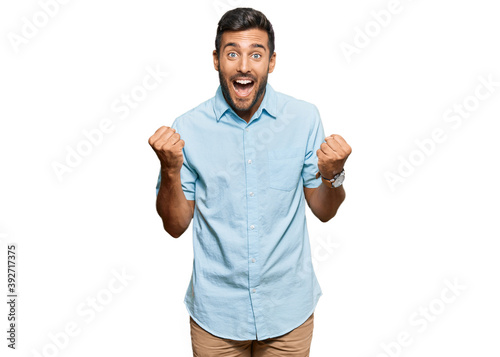 Handsome hispanic man wearing casual clothes celebrating surprised and amazed for success with arms raised and open eyes Poster Mural XXL