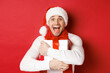 Leinwandbild Motiv Concept of winter holidays, christmas and lifestyle. Close-up of happy man in santa hat receiving present, looking happy and hugging gift box, standing over red background