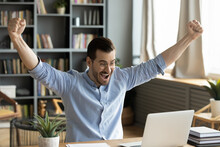 Happy Businessman Looks At Laptop Screen Read Great E-mail News Raised Arms Up Celebrates Career Advance Seated At Desk. Success At Business, Online Auction Win. Opportunity, Moment Of Victory Concept