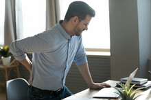 Businessman Touches Lower Back Feeling Pain Sudden Ache While Get Up Out Of Office Chair, Muscular Spasm, Strain Caused By Sedentary Lifestyle, Prolonged Inactivity, Sit In Incorrect Posture Concept