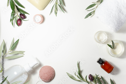Obraz Spa and beauty. A set of cosmetics for care. Soap, cream, towel, shampoo, sponge and olive tree sprigs are arranged around the perimeter on a white background. - fototapety do salonu