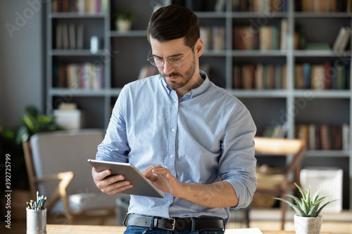 Obraz Focused serious businessman freelancer in glasses standing in modern office lean on table hold tablet device texting message to client, web surfing on-line, makes business offer to partner by e-mail - fototapety do salonu