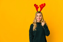 Young Blonde Caucasian Woman Wearing Reindeer Horns Smiling And Raising Thumb Up