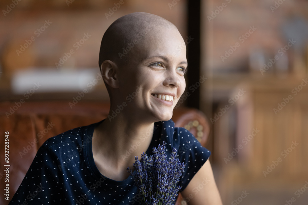 Fototapeta Winning the fight for life. Happy overjoyed young woman recovering after cancer sitting on cozy sofa at home looking at distance dreaming believing hoping for best holding bunch of lavender in hands