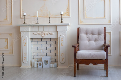 Photo Wooden beige armchair stands next to fireplace