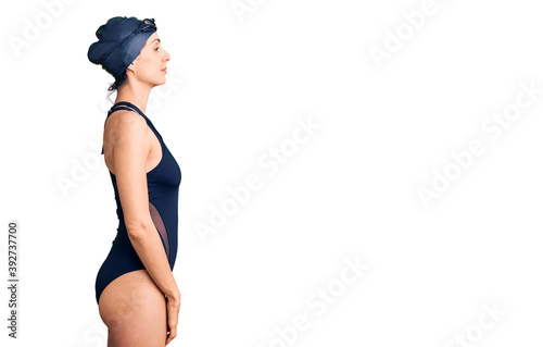 Fotografering Young beautiful hispanic woman wearing swimwear and swimmer glasses looking to side, relax profile pose with natural face with confident smile