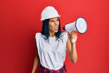 Young African American Worker Woman Screaming Using Megaphone Over Isolated Red Background.