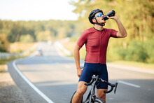 Muscular Cyclist Relaxing On Bike And Drinking Water