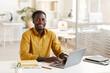 Portrait of smiling African-American man using laptop and looking at camera while enjoying work in minimal office interior, copy space