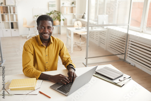 Obraz High angle portrait of smiling African-American man using laptop and looking at camera while enjoying work in minimal office interior, copy space - fototapety do salonu