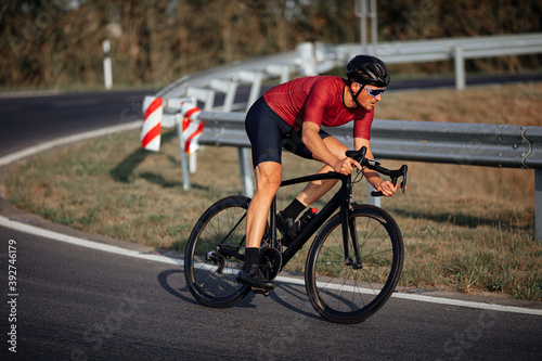 Foto Active young cyclist racing on paved road