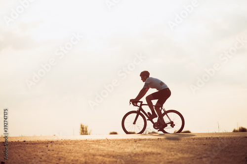 Leinwand Poster Active cyclist in sport clothing racing on road