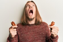 Handsome Caucasian Man With Long Hair Eating Chicken Wings Angry And Mad Screaming Frustrated And Furious, Shouting With Anger Looking Up.