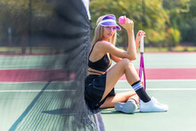 A Lovely Blonde Model Plays Tennis On A Hot Summers Day
