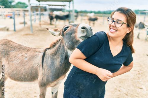 Carta da parati Hispanic woman playing with donkey at the farm.