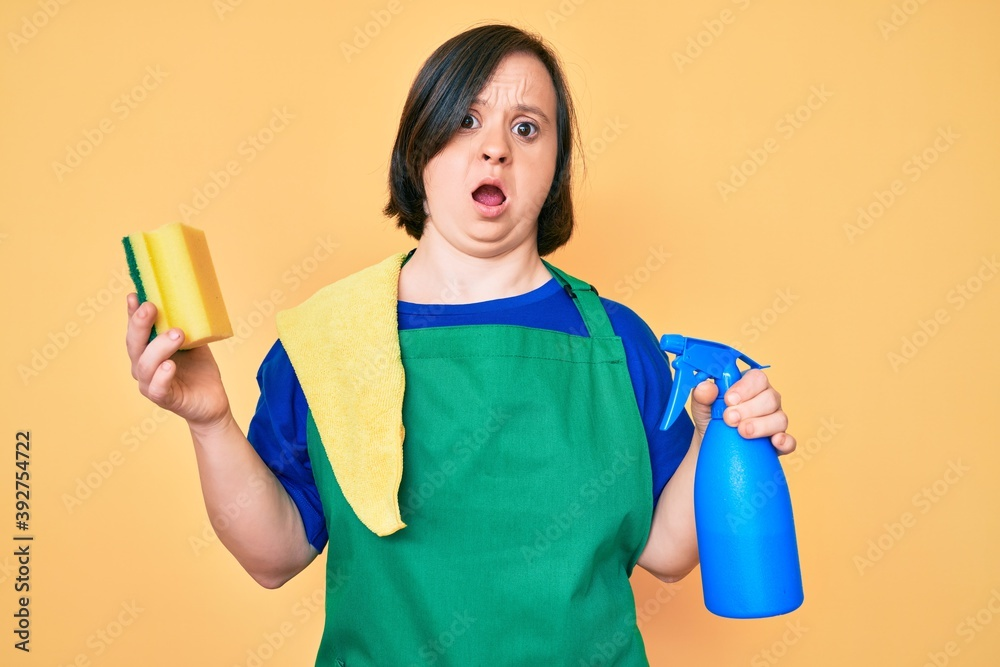 Fototapeta Brunette woman with down syndrome wearing apron holding scourer in shock face, looking skeptical and sarcastic, surprised with open mouth