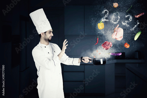 Male chef cooks with flying foods and numbers 2021