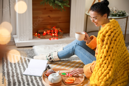 Fotomural Beautiful young woman with warm plaid reading book and drinking tea at home