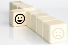 Close Up Custome Choose Face And Blurred Sad Face Icon On Wood Cube, Service Rating, Satisfaction Concept.