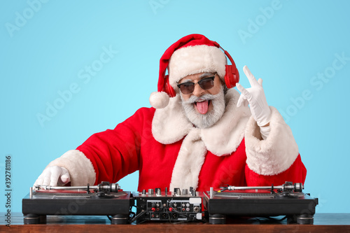 Photo Cool Santa DJ playing music on color background